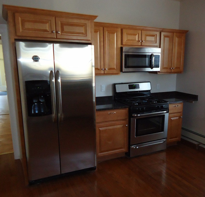 Newly_renovated_kitchen_with_cabinets_refrigerator_stove_and_hardwood_floor