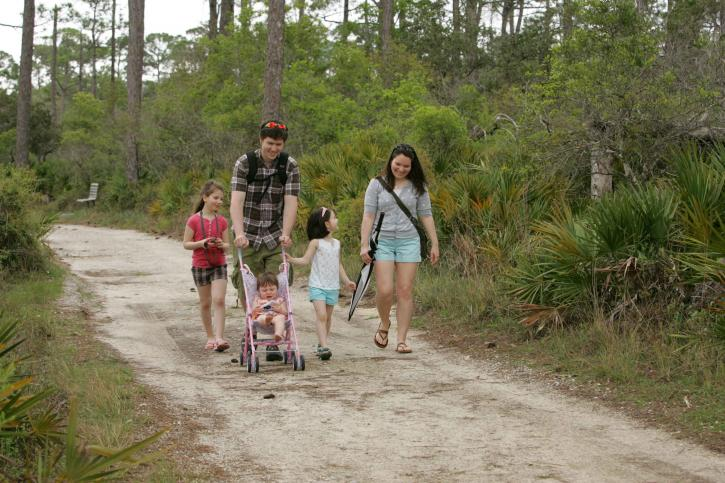 family-enjoys-strolling-on-the-paths-at-the-park-725x483