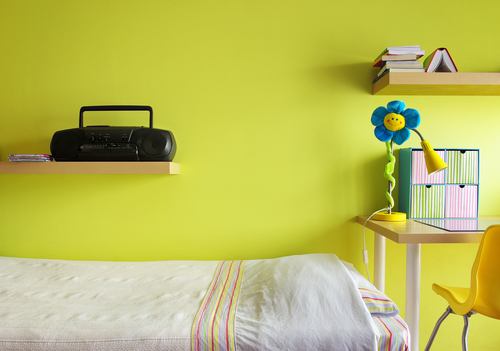 Detail of a teenager bedroom with desk, bed, shelf, and yellow wall